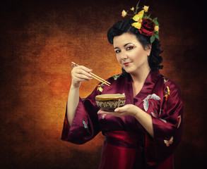 Flowers haired kimono woman eating with chopsticks