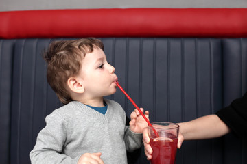 Mother giving fruit drink to her son