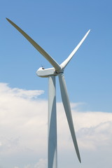 close - up wind turbine on a field with blue sky