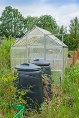 Allotment garden green house with compost bins