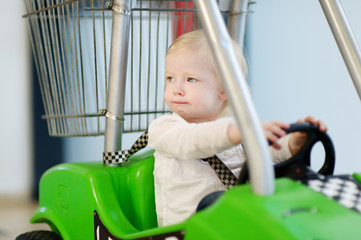 Adorable girl sitting in shopping cart