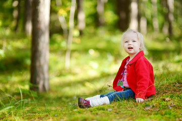 Adorable toddler girl sitting in the forest
