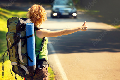Girl wearing backpack holding map, hitch hiking. - 66352827