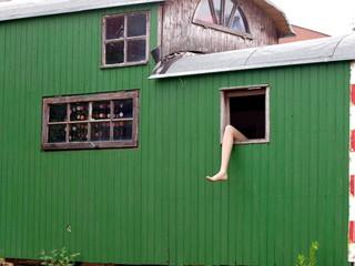 Frauenbein hängt aus einem der Fenster