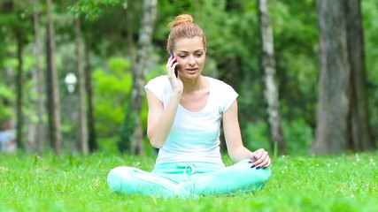 Young woman doing yoga after a telephone conversation in park.