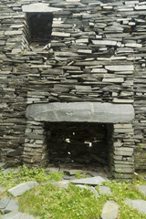 Old fireplace in ruined slate house