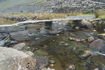 Old stone clapper bridge over mountain stream.