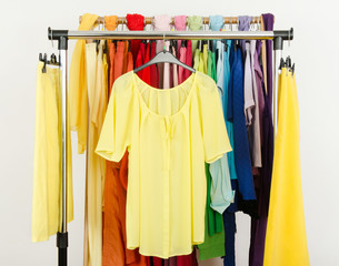 Cute yellow blouse and skirts displayed on a rack.