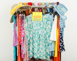 Cute summer outfits displayed on hangers with a big sale sign.