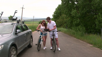 Young couple with bicycles near his car looking at map
