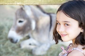 Primer plano de niña con burro en establo de fondo