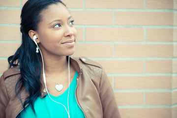 beautiful african young woman listening music earphones