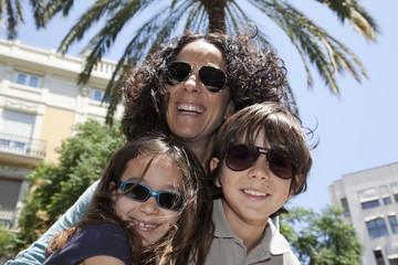 Madre e hijos con gafas de sol en contrapicado