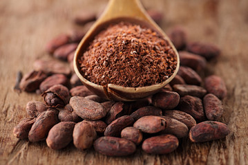 cocoa powder in spoon on roasted cocoa chocolate beans backgroun