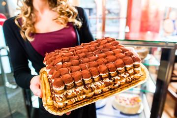 Bäckerin präsentiert Tiramisu in Patisserie