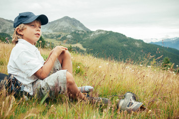 Young boy takes a rest in a meadow during a mountain trek.