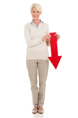 senior woman holding red arrow pointing down