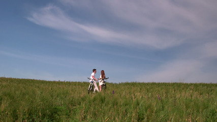 Young couple with bicycles in the green field