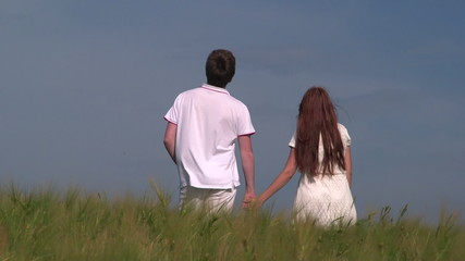 Young couple holding hands in wheat field