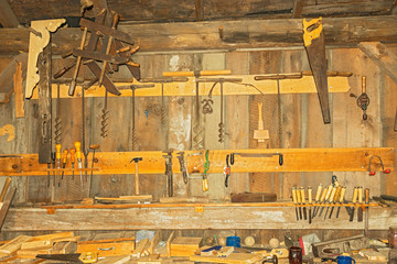 very old rusty woodworking tools on the wall in the workshop