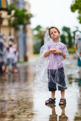 Little boy standing under the rain