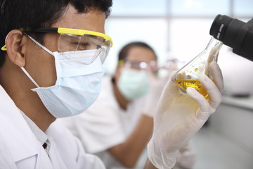 Chemist holding sample of liquid in laboratory