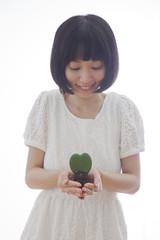 ハート型の植物を持つ女性