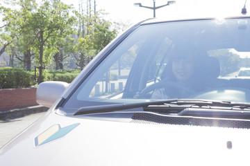 初心者マークを貼って運転する女性
