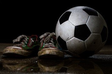 Dirty sneakers with soccer ball on black background