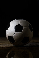 Isolated dirty soccer ball on black bavkground