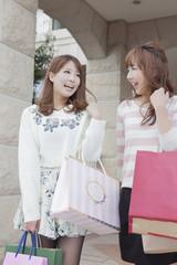 友達とショッピングバッグを持って会話をする女性