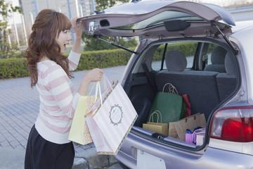 車のトランクを開けて驚く女性