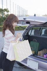 車のトランクを開ける女性