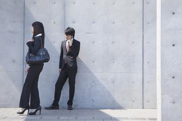 電話をするビジネスと歩くビジネスウーマン
