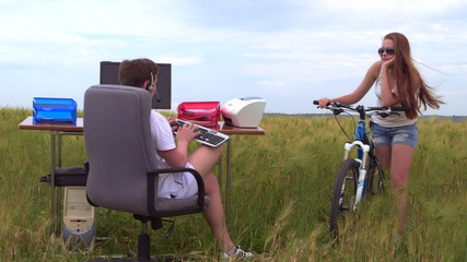girl with bicycle looking at the guy behind a computer in field