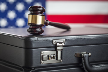 Briefcase and Gavel Resting on Table with American Flag Behind