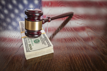 Wooden Gavel Resting on Money with American Flag Reflection