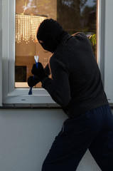 Burglar trying to open a window