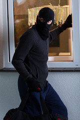 Burglar looks around and opening a window