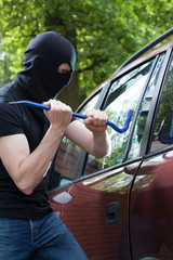A thief breaking into a car
