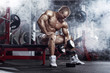 bodybuilder athletic guy execute exercise biceps with dumbbells
