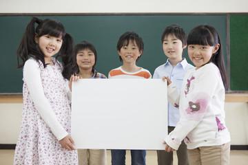 ホワイトボードを持つ小学生