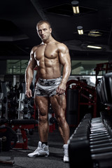 very power muscular bodybuilder guy posing in the gym