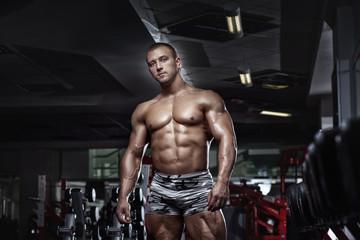 Muscular bodybuilder guy posing in the gym