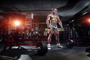 bodybuilder athletic guy standing with barbell workout in gym