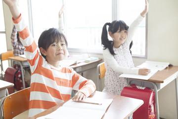 手をあげる小学生