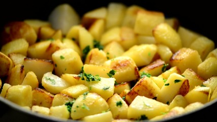 Roasting potatoes in a pan close up shoot