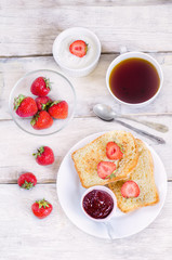 breakfast with fresh toasts, strawberries and strawberry jam