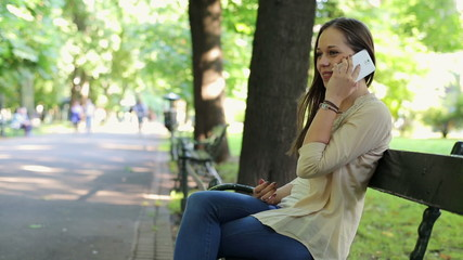 Young woman talking on cellphone in the city park