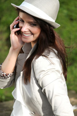 Beautiful brunette young woman outdoor with hat on calling
